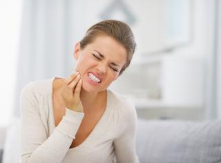 Woman experiencing toothache who needs to see emergency dentist in Prairieville