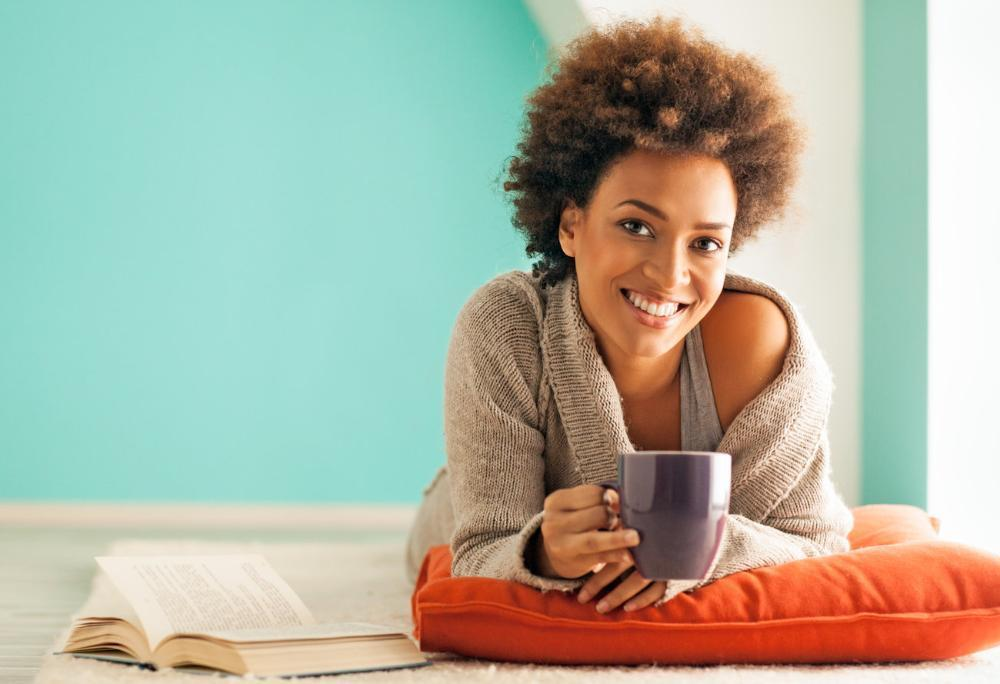 Woman holding coffee smiling | Dentist Baton Rouge