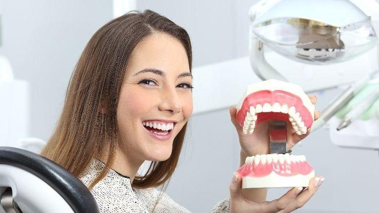 woman holding fake teeth | cosmetic dentistry prairieville la
