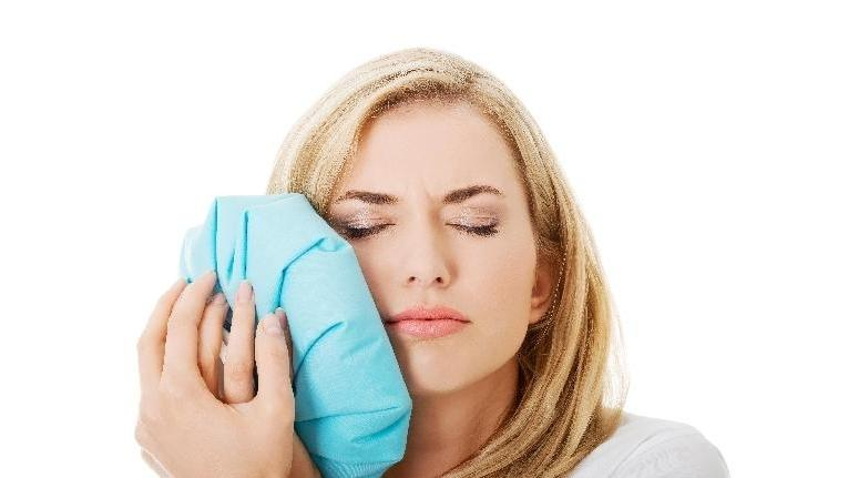 woman holding ice pack to her mouth | tmj treatment prairieville la